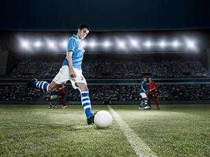 Soccer player kicking ball on fieldの写真素材 [FYI02158764]