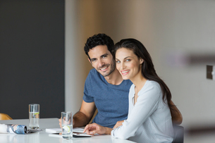 Portrait of smiling couple paying bills at tableの写真素材 [FYI02158774]