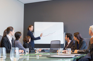 Businesswoman drawing graph for colleagues in meetingの写真素材 [FYI02158849]