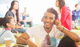 University student listening to headphones in loungeの写真素材 [FYI02158888]