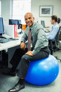 Businessman sitting on fitness ball in officeの写真素材 [FYI02158927]
