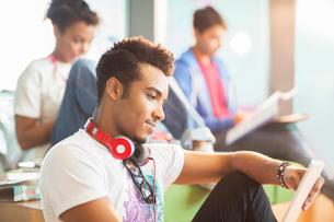 University student using digital tablet in loungeの写真素材 [FYI02158957]