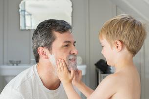 Boy rubbing shaving cream on father's faceの写真素材 [FYI02158977]
