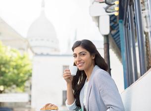 Woman drinking espresso at sidewalk cafe near Sacre Coeur Basilica, Paris, Franceの写真素材 [FYI02159109]
