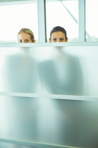 Businesswomen peeking over half wall in officeの写真素材 [FYI02159182]