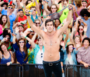 Fans cheering behind performer on stage at music festivalの写真素材 [FYI02159235]