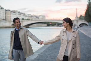 Couple holding hands along Seine River, Paris, Franceの写真素材 [FYI02159270]