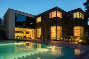 Modern house and swimming pool illuminated at duskの写真素材 [FYI02159279]