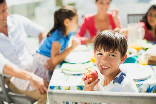 Boy eating fruit with family at table on sunny patioの写真素材 [FYI02159302]