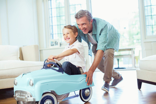 Father pushing son in toy carの写真素材 [FYI02159342]