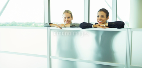 Smiling businesswomen leaning against half wall in officeの写真素材 [FYI02159356]