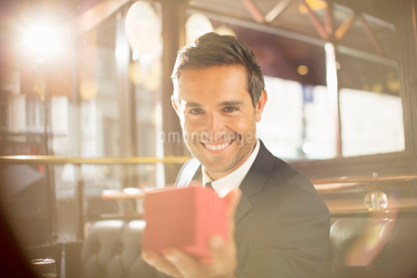 Well-dressed man holding jewelry box in restaurantの写真素材 [FYI02159385]