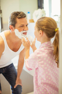 Girl rubbing shaving cream on father's faceの写真素材 [FYI02159402]