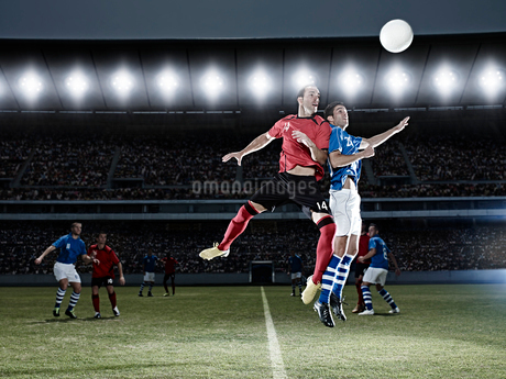 Soccer players jumping for ball on fieldの写真素材 [FYI02159495]