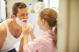 Girl rubbing shaving cream on father's faceの写真素材 [FYI02159518]
