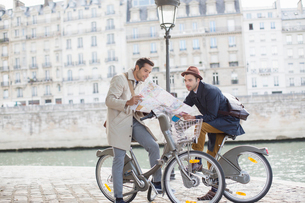 Men on bicycles reading map along Seine River, Paris, Franceの写真素材 [FYI02159578]
