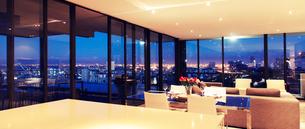 Illuminated modern living room overlooking cityの写真素材 [FYI02159581]