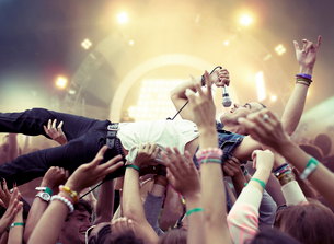 Performer crowd surfing at music festivalの写真素材 [FYI02159603]