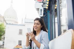 Woman using cell phone at sidewalk cafe near Sacre Coeur Basilica, Paris, Franceの写真素材 [FYI02159816]