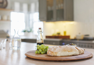 Baguette, balsamic vinegar and grapes on wooden board in kitchenの写真素材 [FYI02159822]
