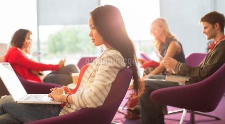 University student using laptop in loungeの写真素材 [FYI02159861]