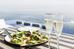 Plate of salad and glasses of champagne on table outdoorsの写真素材 [FYI02159890]