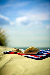 Open book on towel at sandy beachの写真素材 [FYI02159946]