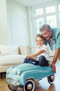 Father pushing son in toy carの写真素材 [FYI02159969]