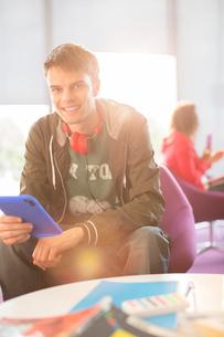 University student using digital tablet in loungeの写真素材 [FYI02159994]