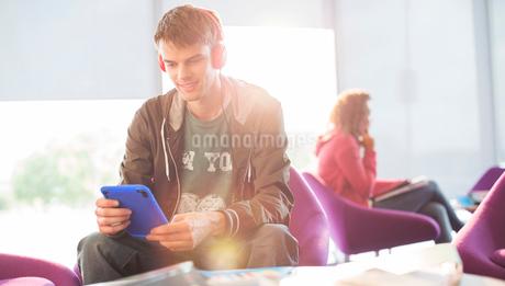 University student listening to headphones in loungeの写真素材 [FYI02160059]