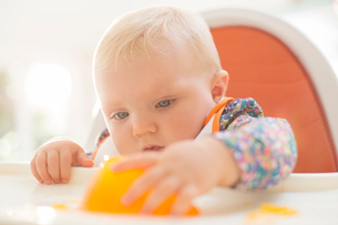 Baby girl playing with gelatin dessert in high chairの写真素材 [FYI02160105]