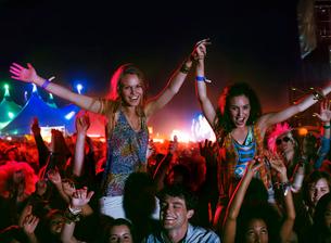 Cheering women on men's shoulders at music festivalの写真素材 [FYI02160179]