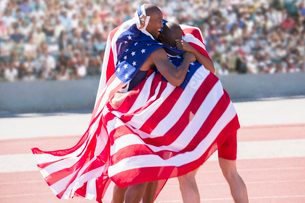 Track and field athletes wrapped in American flag on trackの写真素材 [FYI02160198]