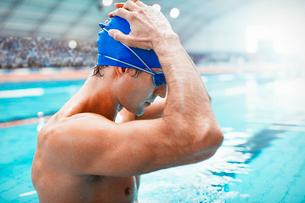 Swimmer adjusting cap at poolsideの写真素材 [FYI02160289]