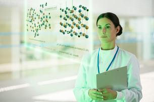 Serious doctor with clipboard in hospital corridorの写真素材 [FYI02160337]