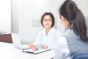 社内にてカウンセリングをする女性社員とカウンセラーの写真素材 [FYI02160461]