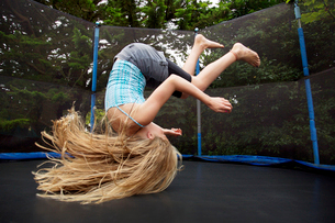 Girl jumping on trampoline outdoorsの写真素材 [FYI02160468]