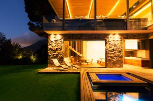 Modern house overlooking illuminated swimming pool at nightの写真素材 [FYI02160484]