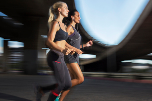 Women running together through city streetsの写真素材 [FYI02160666]