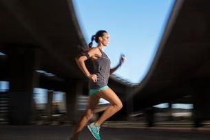 Woman running through city streetsの写真素材 [FYI02160672]