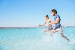 Couple running in water on beachの写真素材 [FYI02160724]
