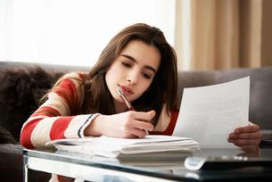 Girl doing homework at coffee tableの写真素材 [FYI02160733]