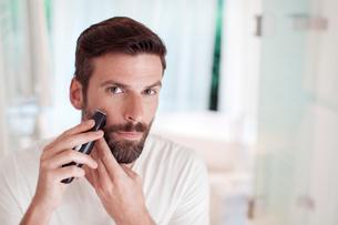 Man trimming beard in bathroom mirrorの写真素材 [FYI02160813]