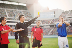 Referee flashing yellow card at soccer player on fieldの写真素材 [FYI02160845]
