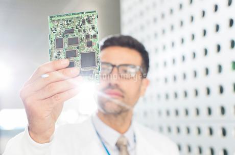 Engineer examining circuit boardの写真素材 [FYI02160940]