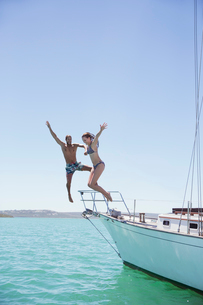 Couple jumping off boat into waterの写真素材 [FYI02160965]