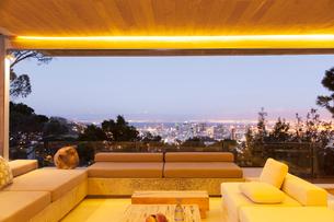 Modern living room overlooking illuminated cityscape at nightの写真素材 [FYI02160986]