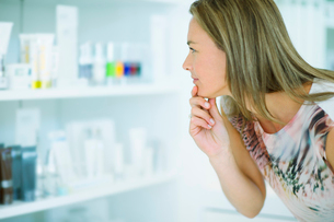 Woman examining skincare products in drugstoreの写真素材 [FYI02161003]