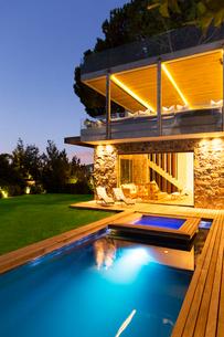 Modern house overlooking illuminated swimming pool at nightの写真素材 [FYI02161040]