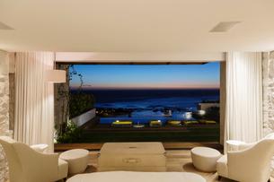 Modern bedroom overlooking ocean at nightの写真素材 [FYI02161088]